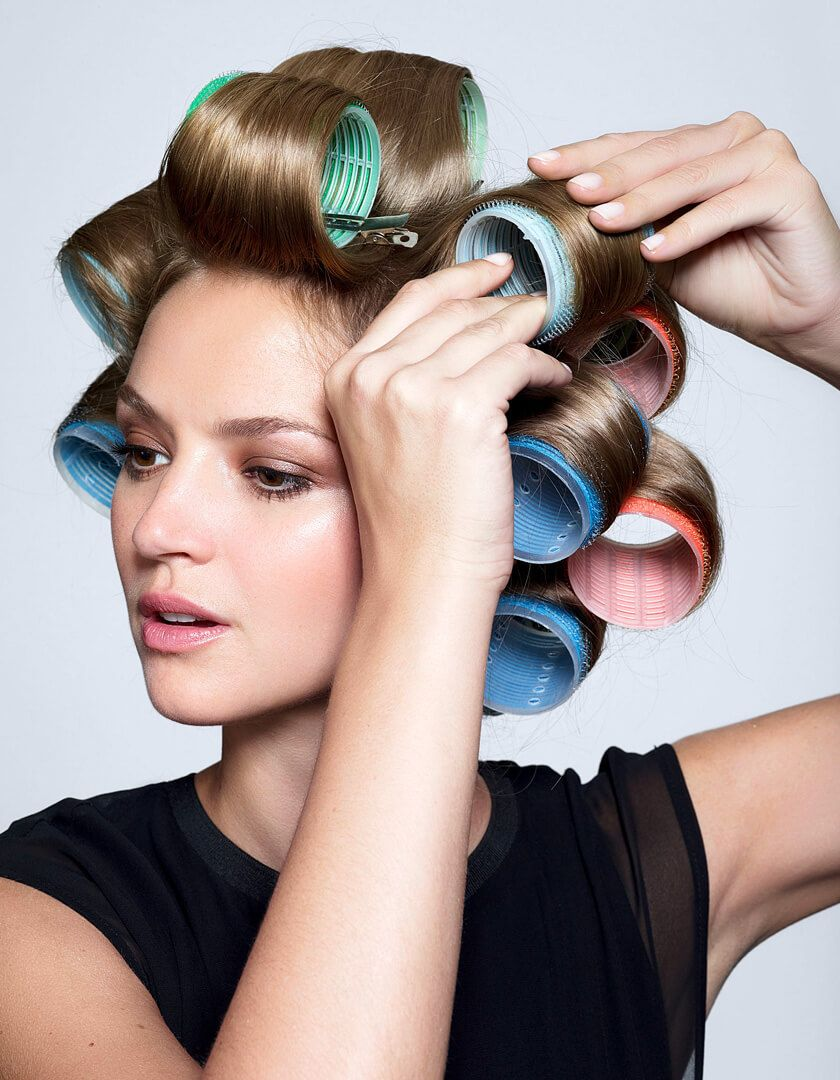 Woman with colorful velcro rollers in hair