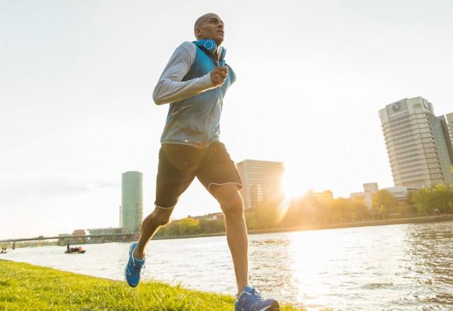 一位慢跑者日落时在河边跑步
