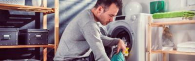men entering clothes into a washing machine