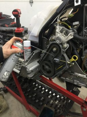 spraying Loctite SF 7635 pro strength degreaser insider a snowmobile chain case