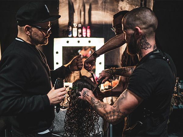 Armin and another hair stylist work on a model's hair at MBFW