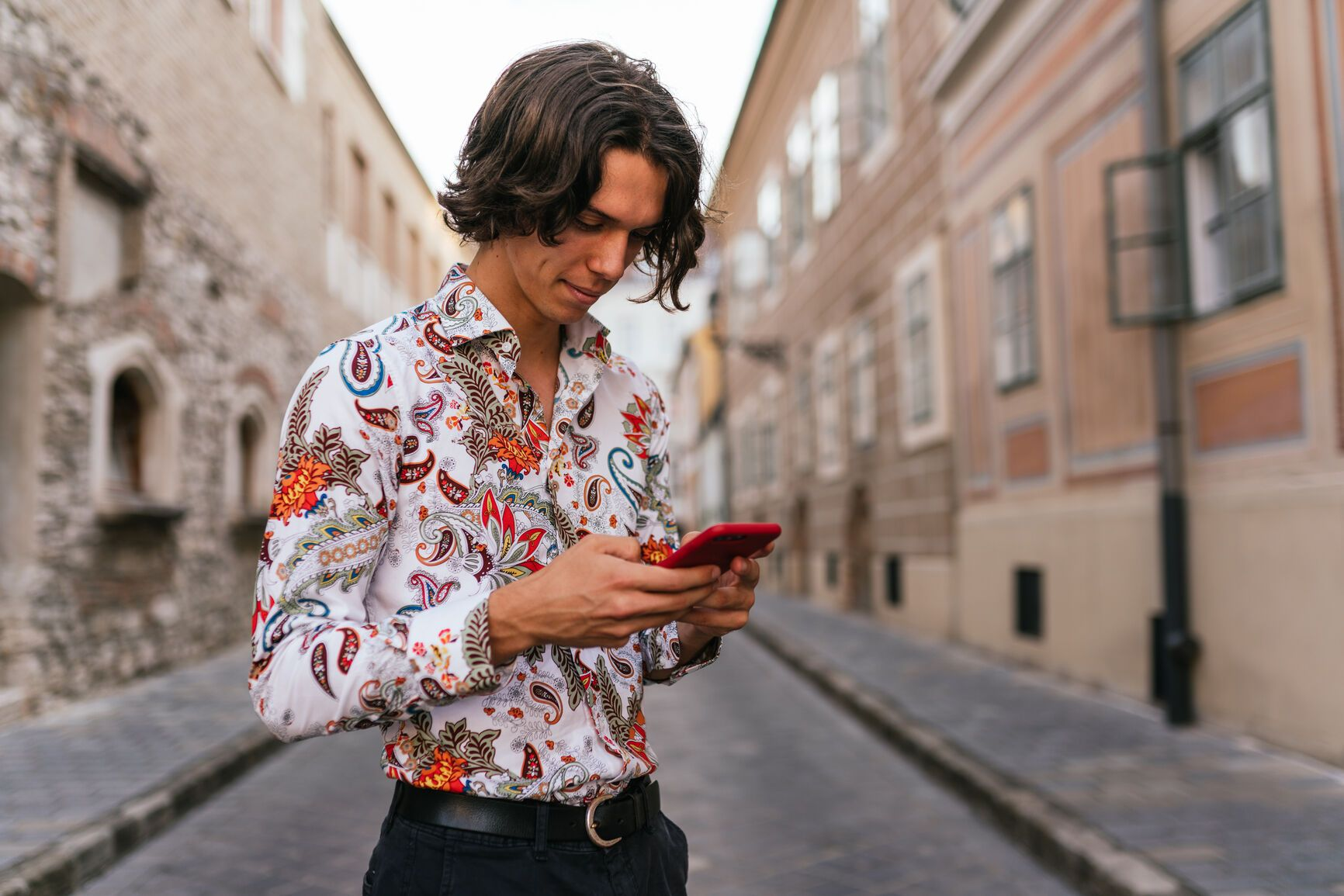A young man with a curtain haircut looking at his phone.