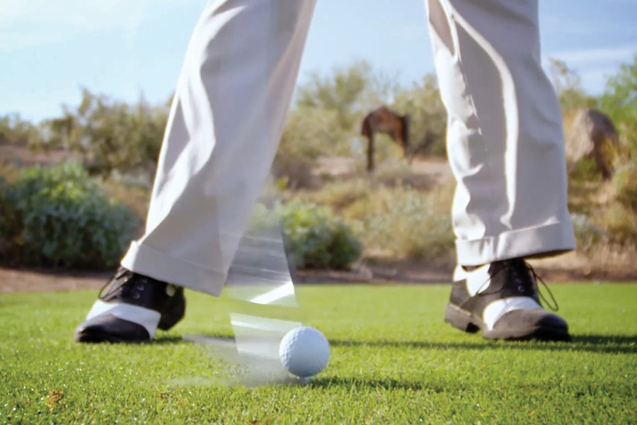 person's feet on golf course, swinging club