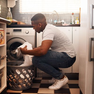 Man looking at his dirty laundry about to insert it into his washing machine