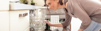 woman in a kitchen smiling looking inside a clean dishwasher