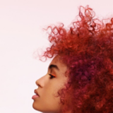 Artful Feeling Side View Of Model With Red Coiled Curls Bob