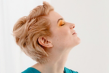 Everyday Decadence Closeup of Model With Light Blonde Wavy Pixie Cut