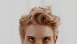 Essential Looks Everday Decadence Model With Light Blonde Wavy Pixie Cut