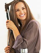 Brunette woman in dressing gown using a flat iron