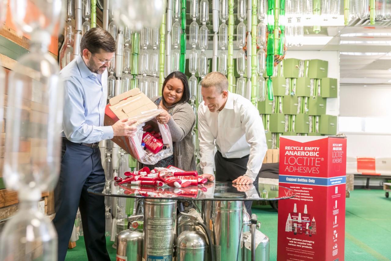 trei oameni care examinează sticle LOCTITE® pregătite pentru reciclare