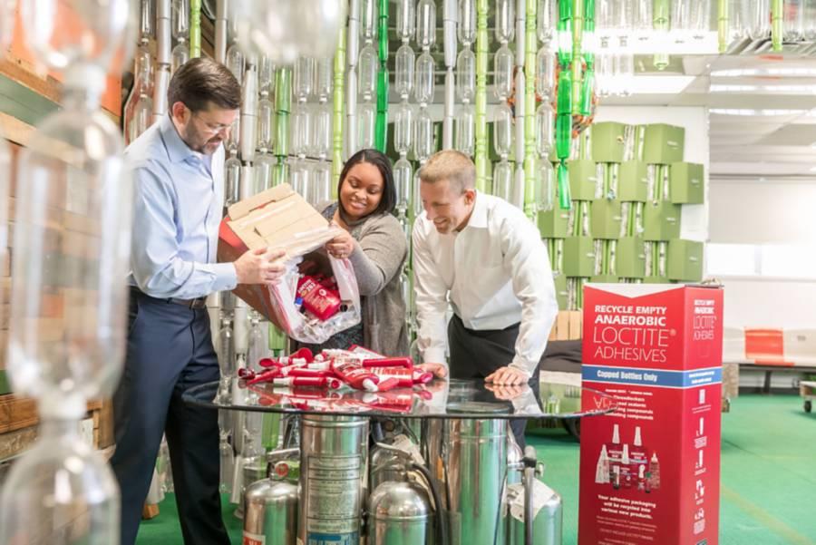 trzy osoby oglądające butelki LOCTITE gotowe do ponownego przetworzenia