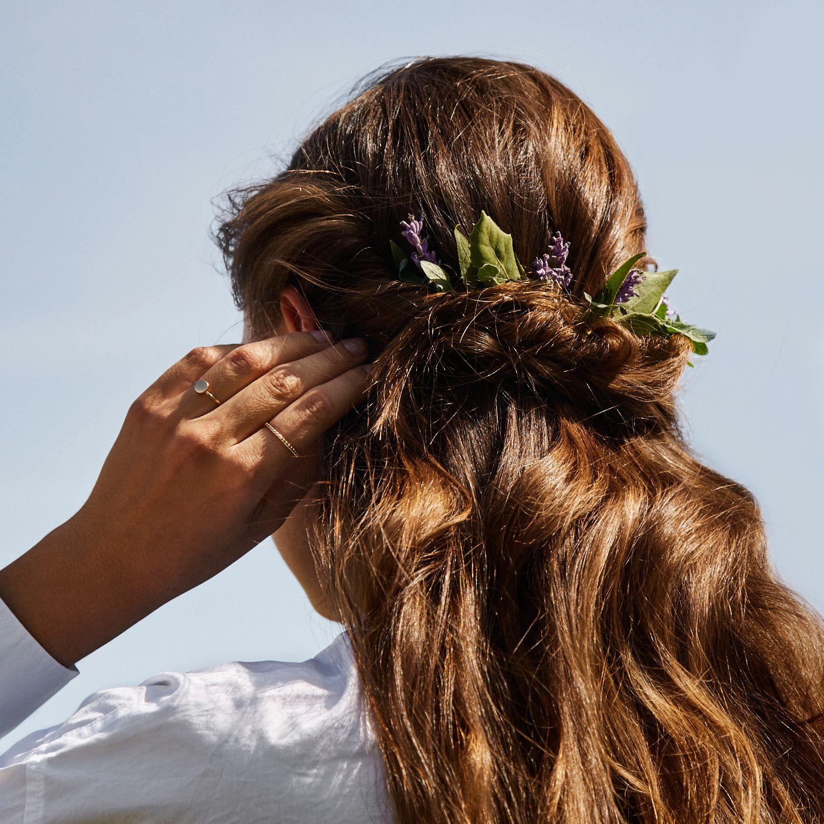 Vue de dos d'une femme aux longs cheveux bruns ornés de lavande