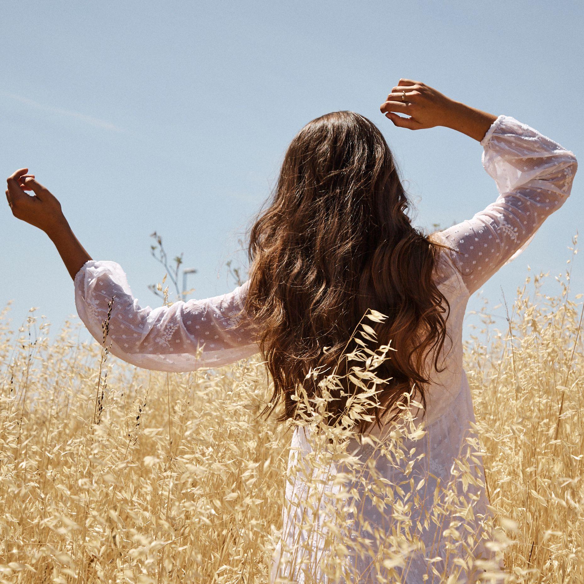 Vue de dos sur une femme aux cheveux longs et bruns en train de danser dans un champ de blé