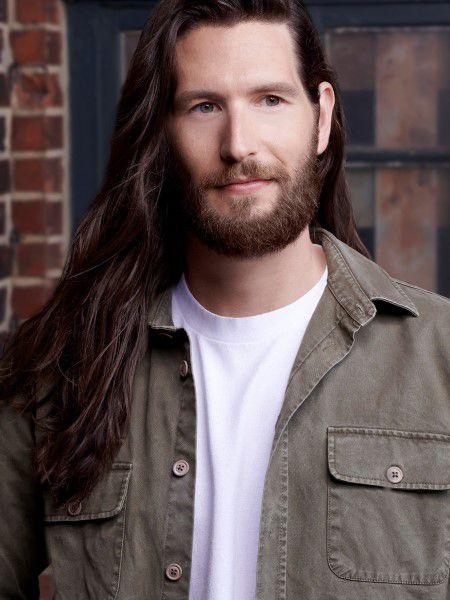 Uomo con barba folta e capelli lunghi