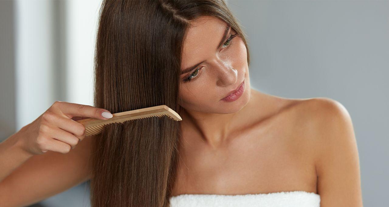 Девушка осторожно расчесывает волосы