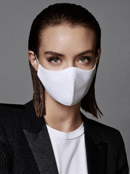 Braunhaarige Frau trägt ihr Haar sleek nach hinten gestylt und trägt eine helle Maske