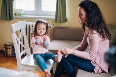 Spiele mit Socken, Frau spielt mit Kind mit Socken an den Händen