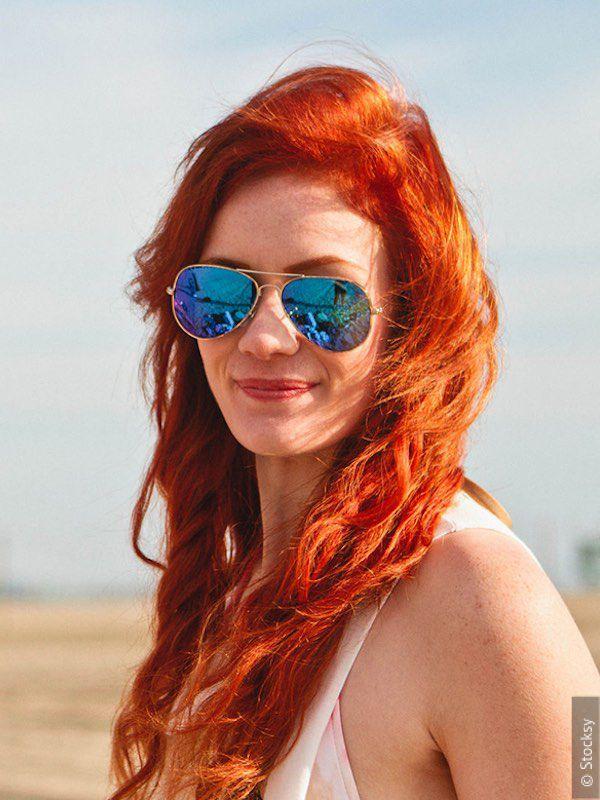 Рыжеволосая девушка в солнцезащитных очках