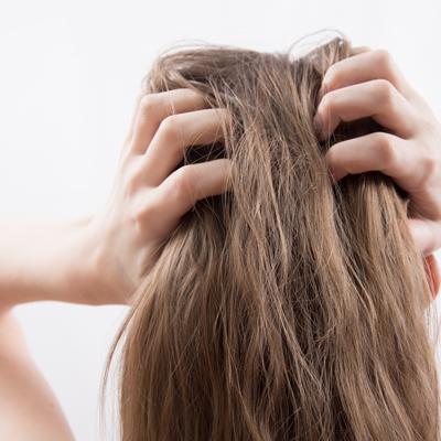 Brunette woman grabbing her scalp