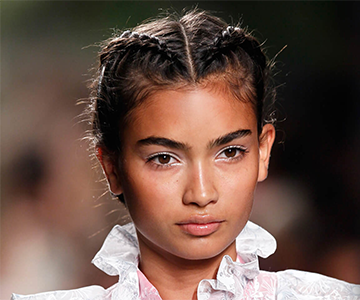 Model on a runway with french plait hairstyle