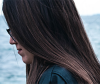 Woman with greasy hair next to the sea