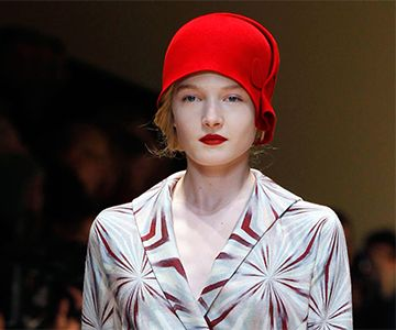 Model wears red winter hat with hair pinned up