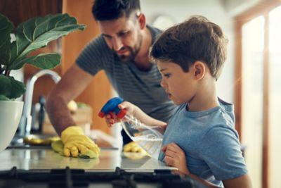 Hausarbeit macht Spass, Mann mit Kind putzen die Küche mit einer Sprayflasche
