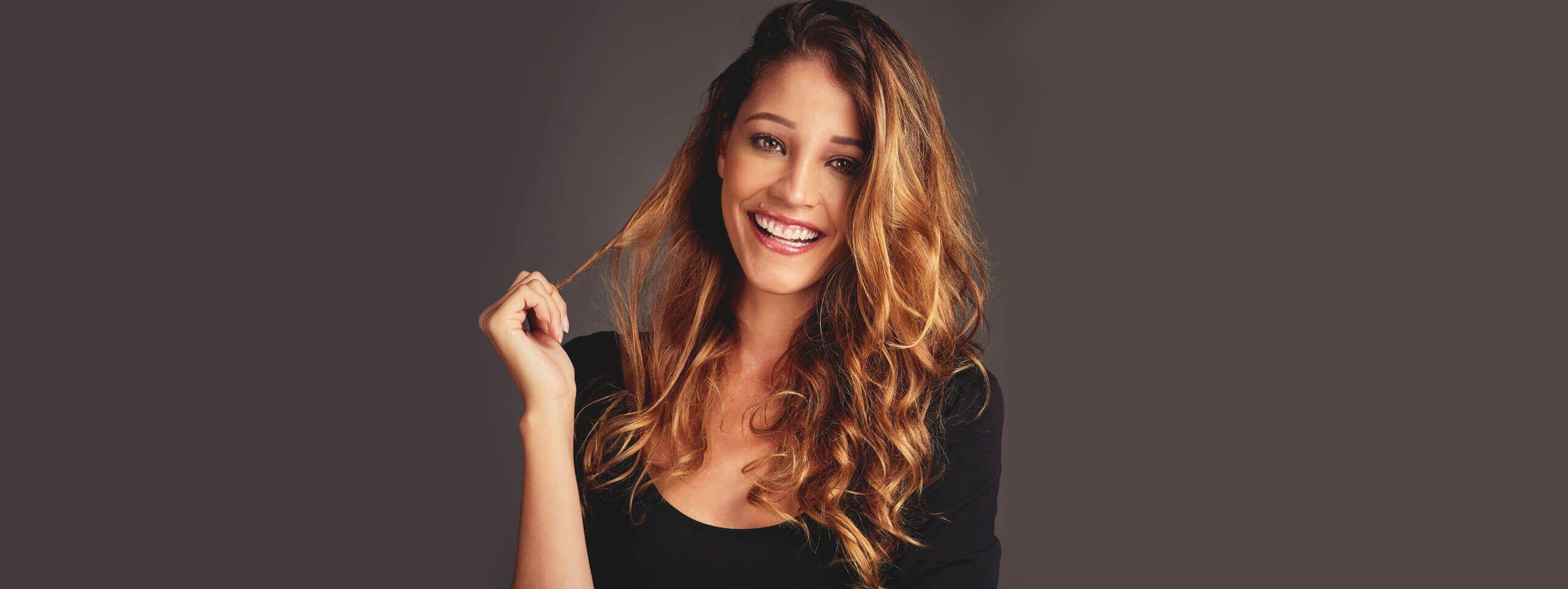 Śmiejąca się kobieta z kręconymi włosami