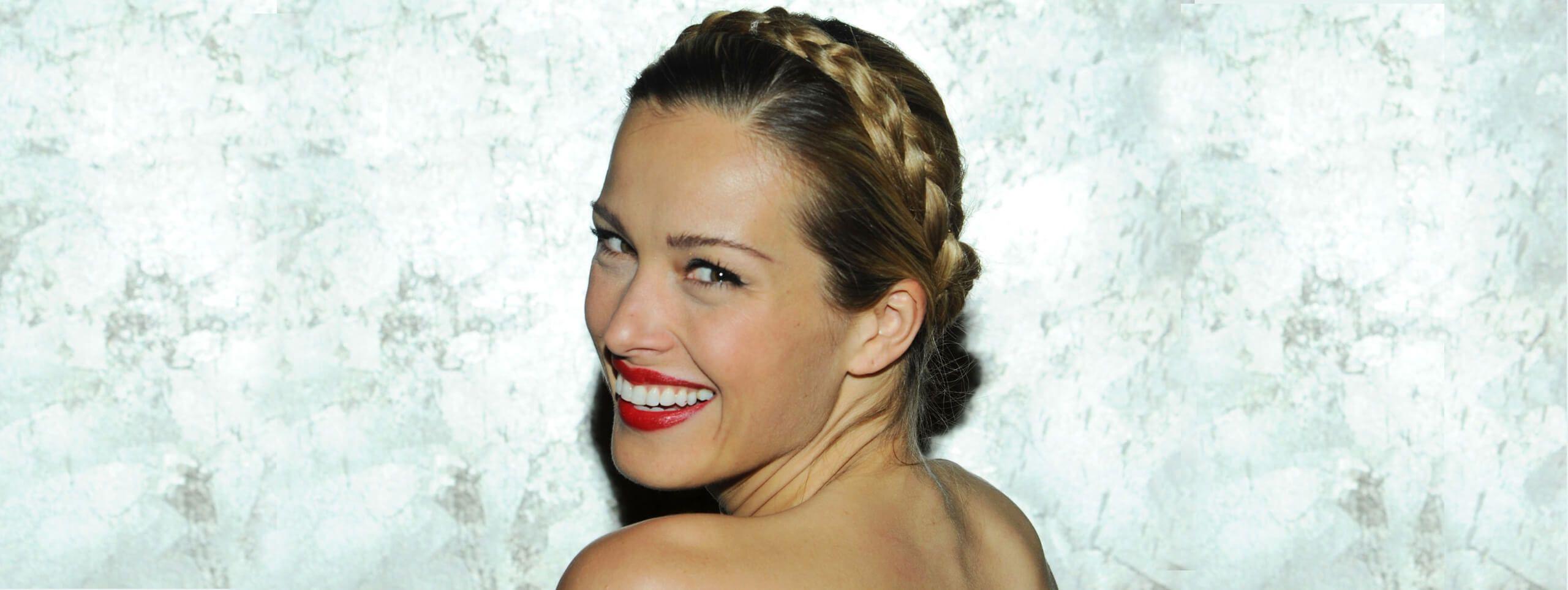 Śmiejąca się kobieta z plecionym upięciem wokół głowy