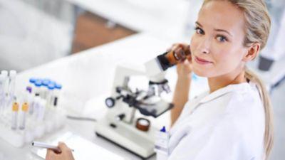 Moteris, vilkinti baltais laboratorijos drabužiais, pakelia akis nuo mikroskopo ir per kairįjį petį pažvelgia į kamerą.