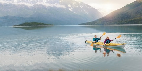 elderly couple sitting in a canoe on a lake with mountains in the background
