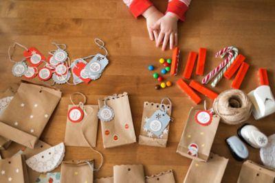 Adventskalender füllen mit schönen Kleinigkeiten, Papiertüten und Bastelsachen liegen auf dem Boden