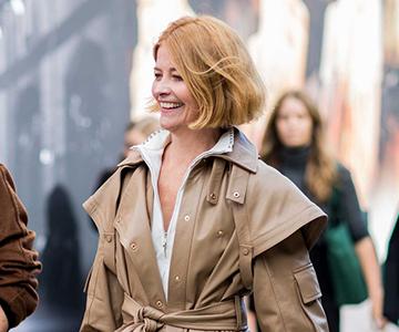 zwei ältere lachende Frauen mit trendigen Frisuren und Mantel