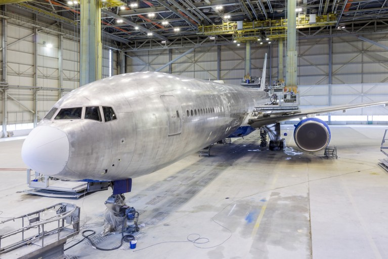Aircraft in maintenance being depainted and then repainted.