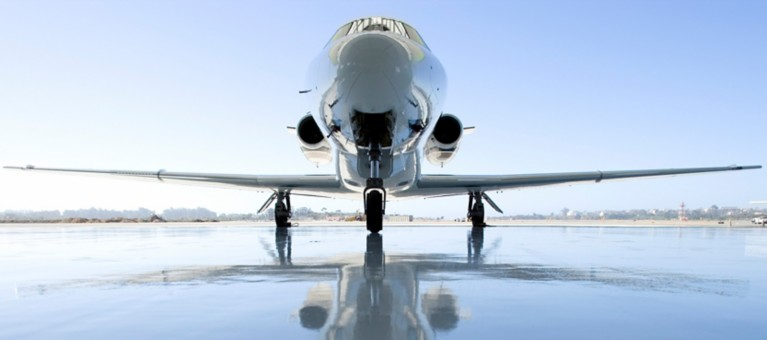 Hero image for aerospace front view of high gloss airplane on reflective surface