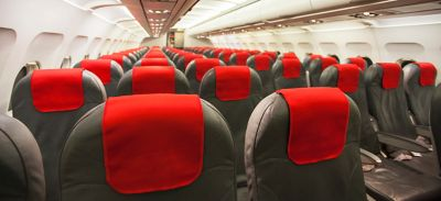 Interior of commercial airplane showing passenger seating grey and red