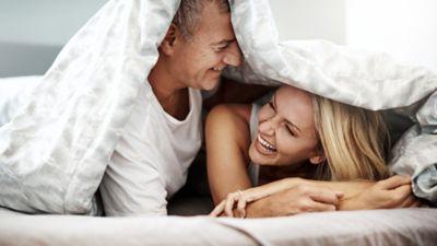 Hygienisch saubere Bettwäsche, Frau und Mann mit Bettdecke