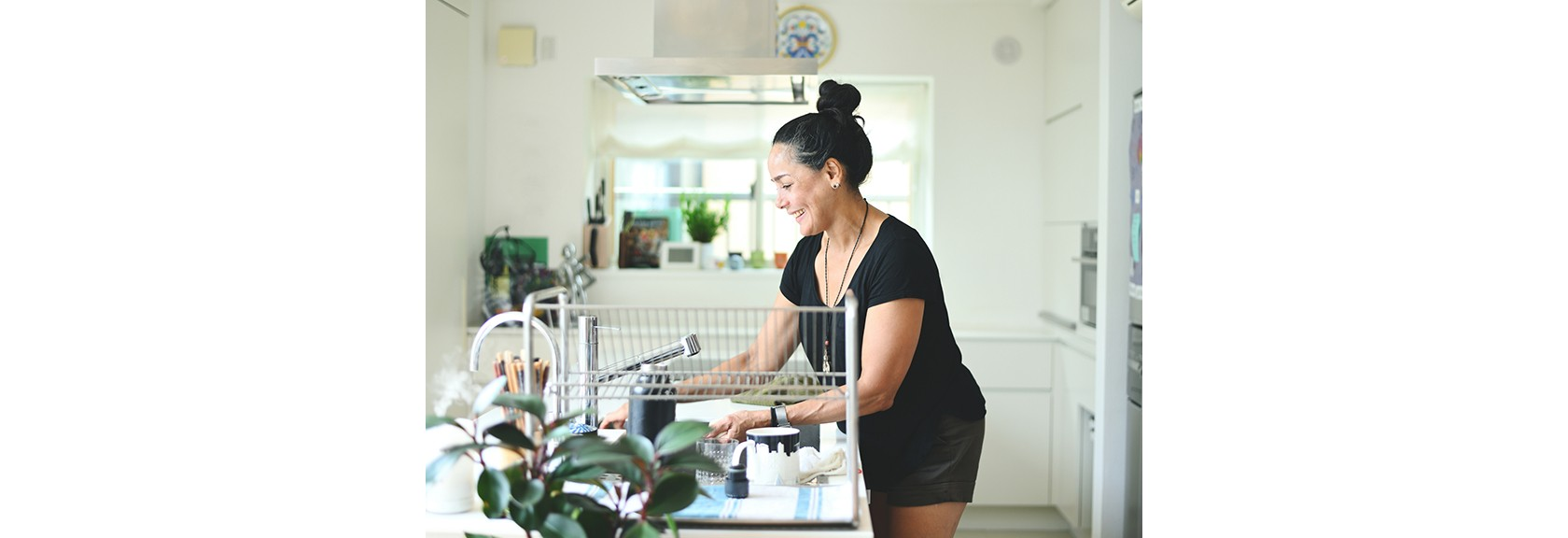 Frühjahrsputz – Küche, Frau reinigt das Waschbecken in der Küche.