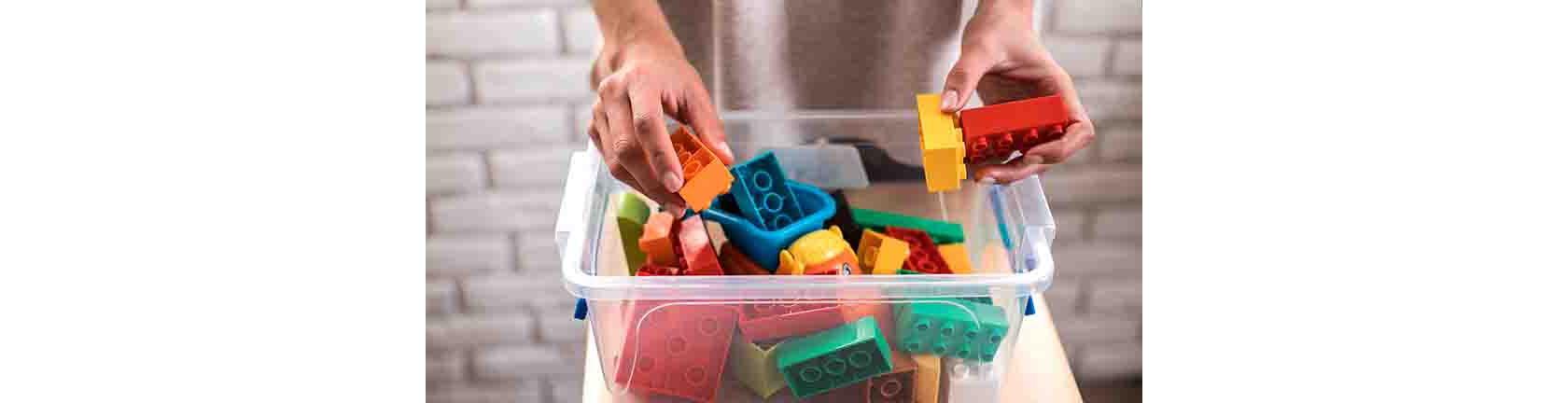 Frühjahrsputz Kinderzimmer, grosse, bunte Legosteine in einer druchsichtigen Kiste.