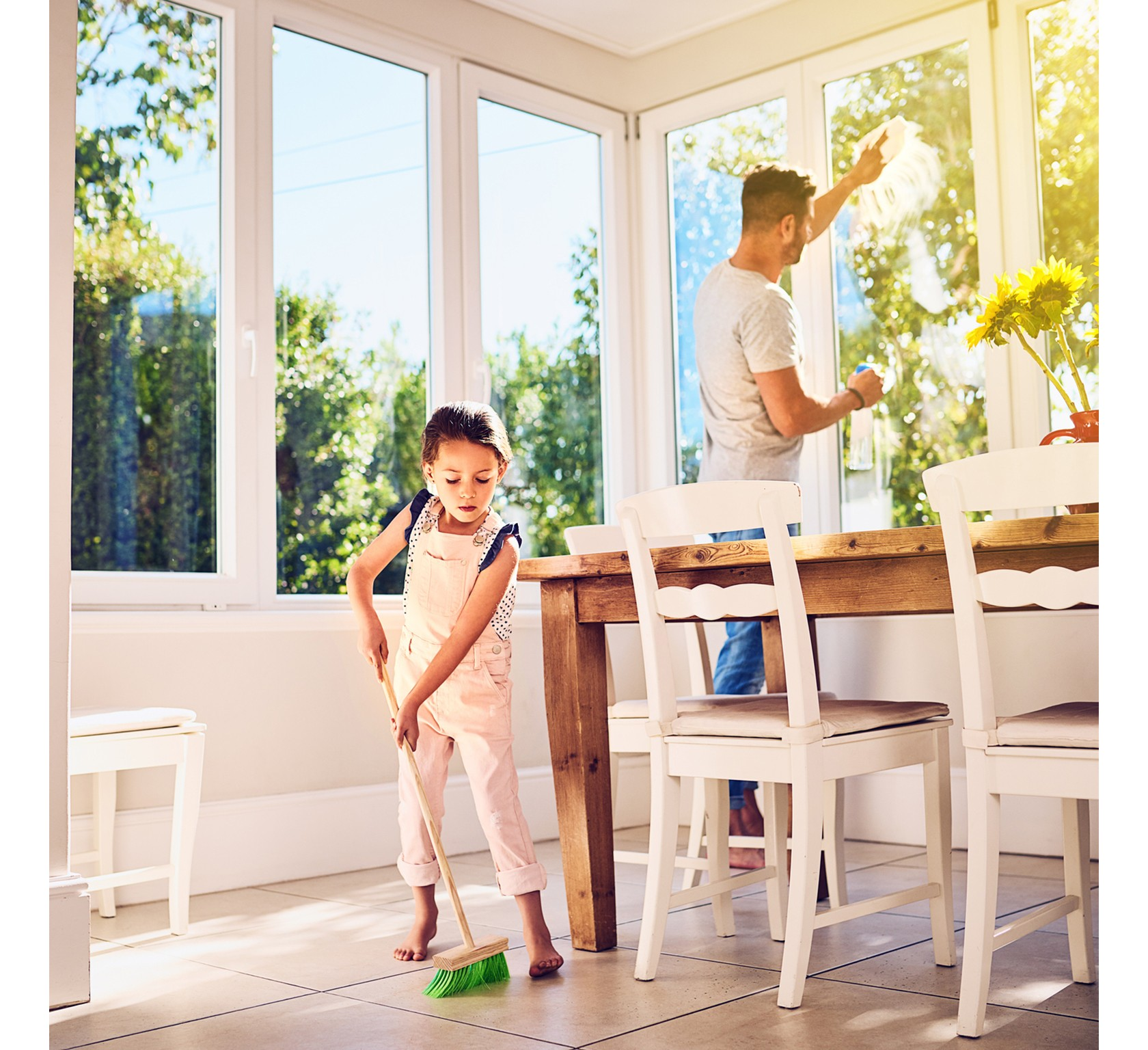 Frühjahrsputz mit der ganzen Familie, Mann putzt Fenster während die Tochter den Boden fegt.