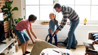 Frühjahrsputz mit der ganzen Familie, Mann und Kinder saugen unterm Teppich