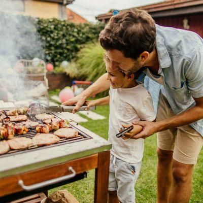 Leitfaden für sicheres Grillen im Sommer. Vater und Sohn grillen im Sommer gemeinsam im Garten.