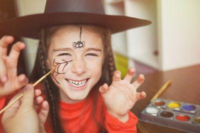 Kleines Mädchen wird als Hexe geschminkt