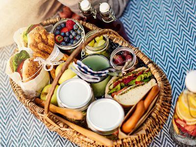 Das perfekte Picknick im Park, ein reichlich gefüllter Picknickkorb mit Essen