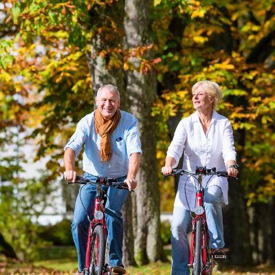 Wie du dein Fahrrad auf Radtouren vorbereitest, Pärchen fährt mit dem Fahrrad auf einer ruhigen Landstraße