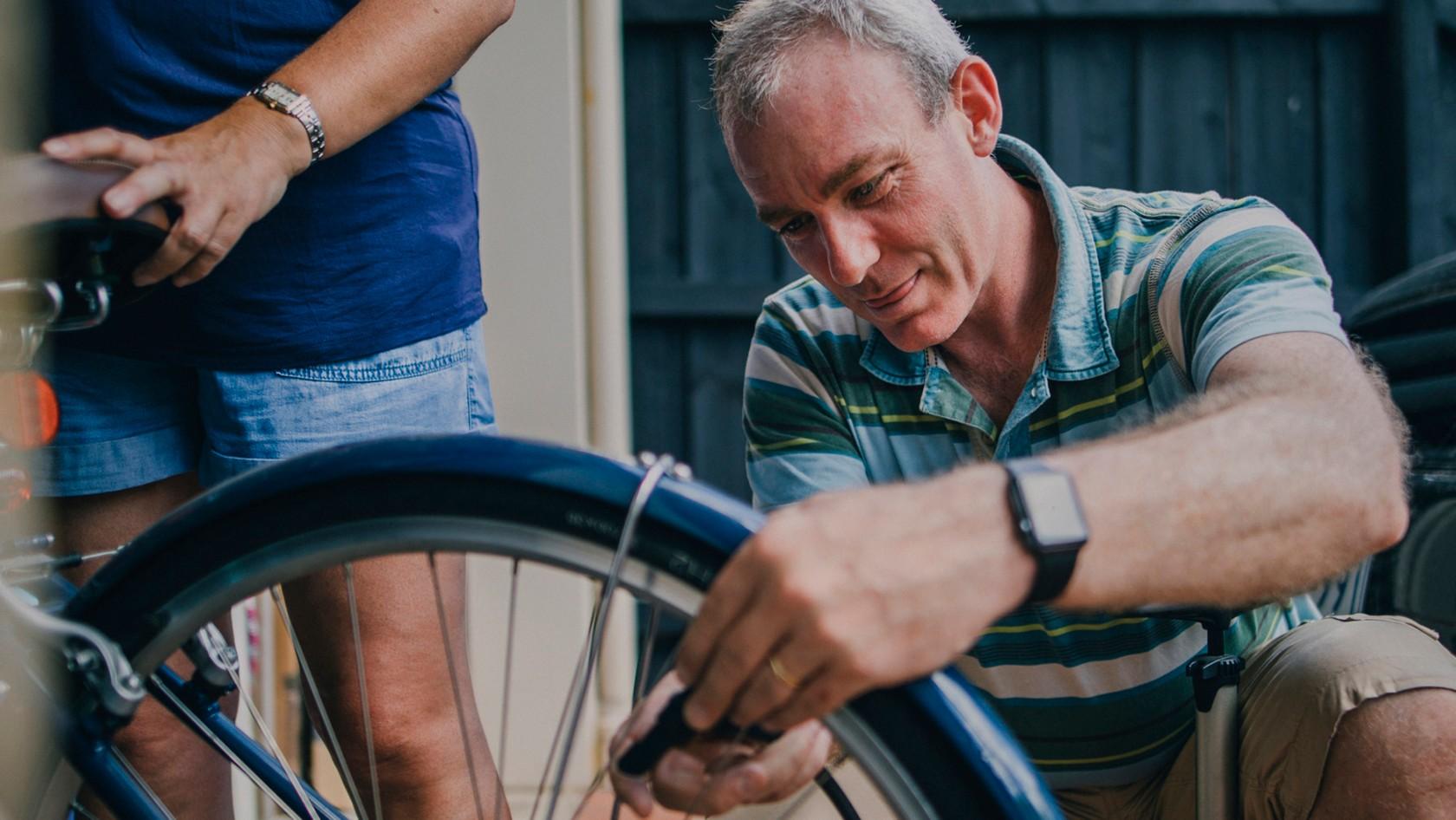 Wie du dein Fahrrad auf den Sommer vorbereitest, Mann pumpt seinen Fahrradreifen auf