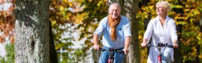 Jak przygotować rower do sezonu, para jadąca na rowerach po spokojnej wiejskiej drodze