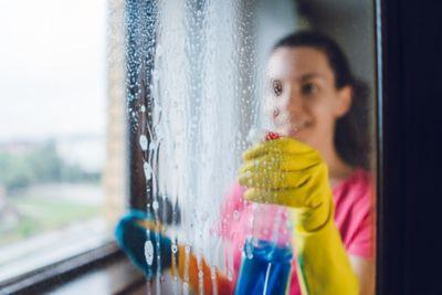 Fenster putzen, Frau sprüht Putzmittel auf Scheibe