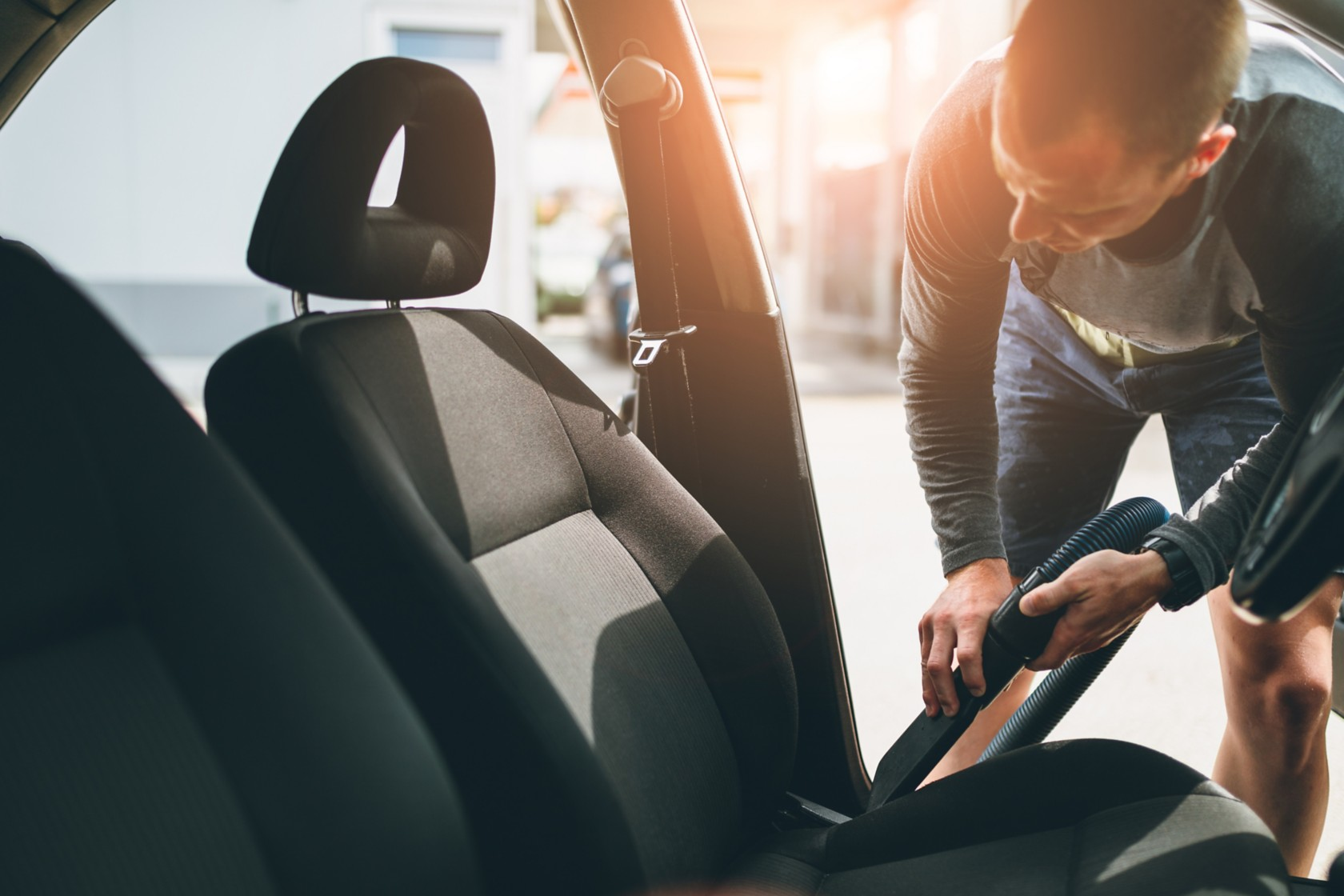 Car seat cleaning, man vacuums crumbs from black car seat