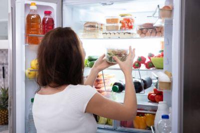 Kühlschrank richtig einräumen, Frau blickt in ordentlichen und gefüllten Kühlschrank